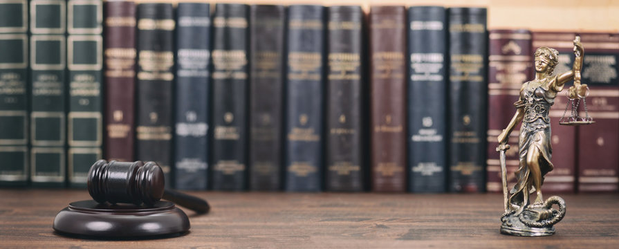 Lady Justice, Scales of Justice and Judge Gavel on a  wooden background.