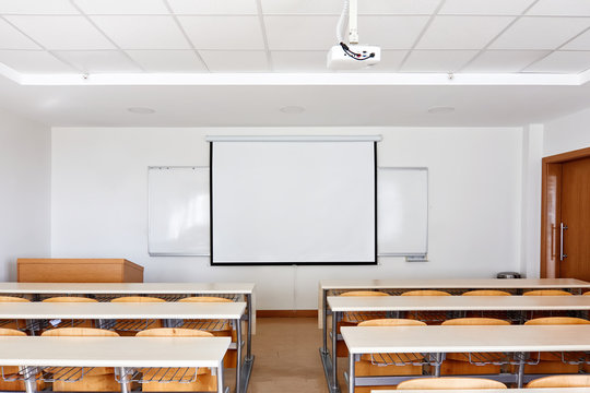 Classroom interior with projection screen, white board and wooden desks