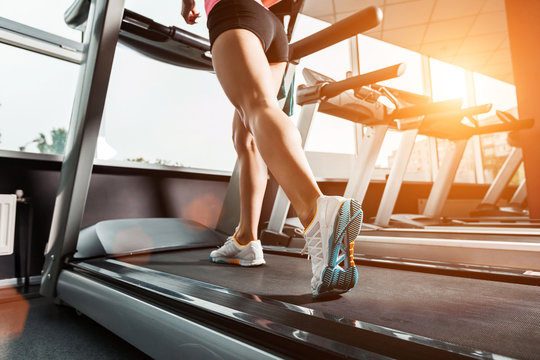 close up girls feet walking at the treadmill in the gym over sunrise. wearing in white orange blue sneakers. Cardio exercise