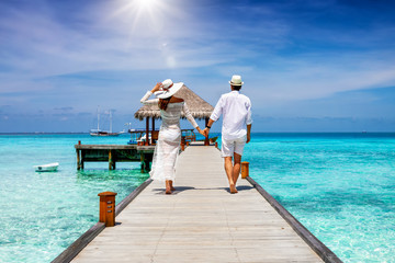 A happy couple in white summer clothing on vacation walks along a wooden pier over tropical, turquoise ocean in the Maldives, Indian Ocean