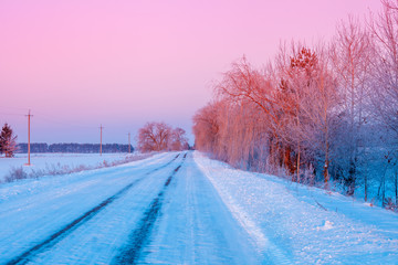Rural winter landscape at sunrise. Country road covered with snow