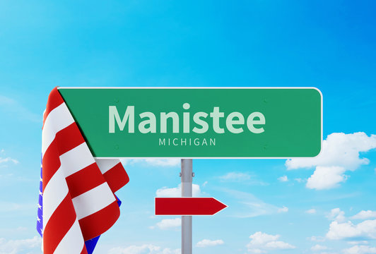 Manistee – Michigan. Road or Town Sign. Flag of the united states. Blue Sky. Red arrow shows the direction in the city. 3d rendering