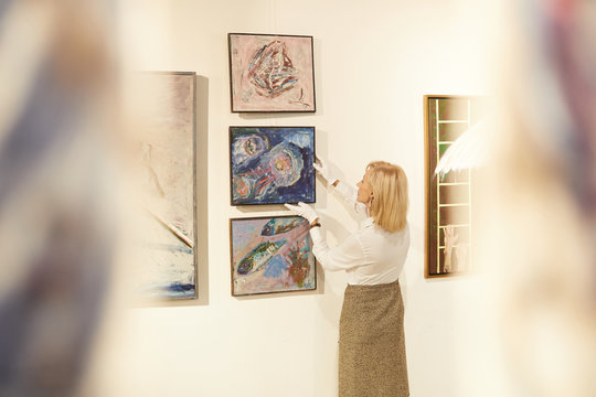 Back view portrait of female art expert hanging paintings while working in art gallery or museum, copy space