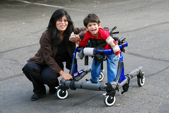 Mother helping disabled son walk in walker outdoors