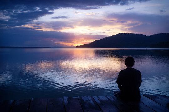 Man sitting on dock with orange sunset on purple blue sky along lake Itza, El Remate, Peten, Guatemala