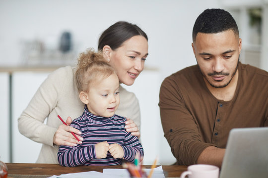 Portrait of smiling mixed-race family using laptop together while shopping online with little girl