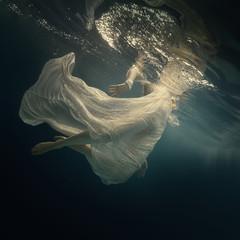 Girl in a beautiful dress swims underwater