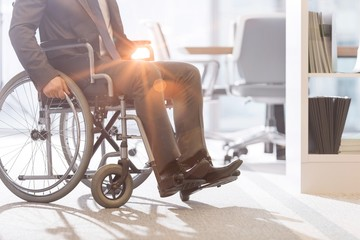 Low angle view of disabled businessman on wheelchair at modern office