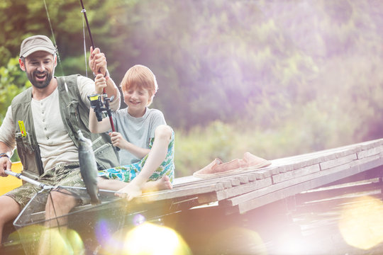 Tilt shot of happy father and son catching fish in butterfly fishing net at lakeshore