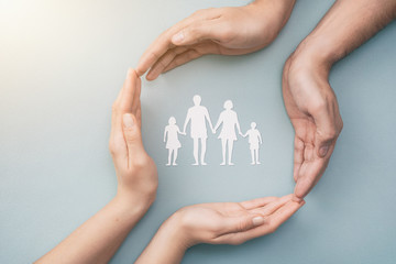 Family care concept. Hands with paper silhouette on table.
