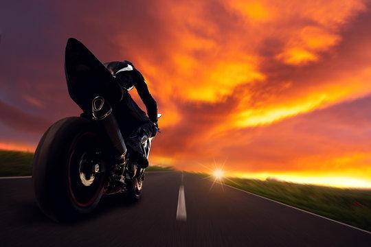 Motorradfahrer fährt rast in den Sonnenuntergang über die Straße