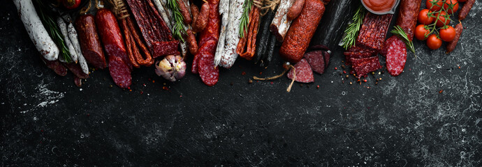Background of salami, sausages and meat products, on black stone background. Top view. Free space for your text. Wall mural