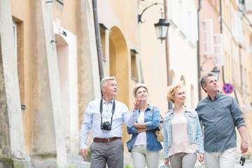 Fototapeta Happy friends talking while walking in city