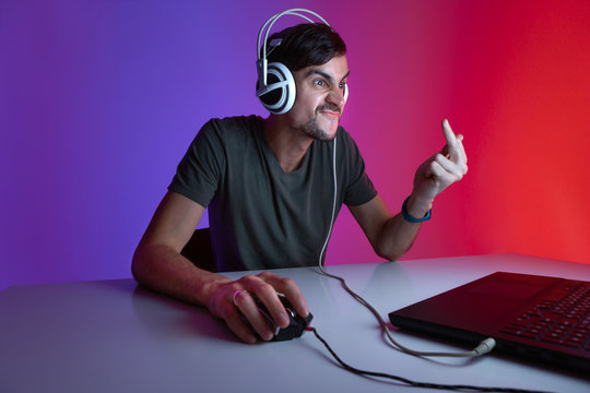 Portrait of an angry gamer playing video games on computer in dark room wearing headphones.