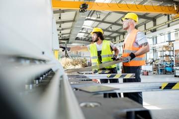 Fototapeta Male manual workers manufacturing sheet metal at industry obraz