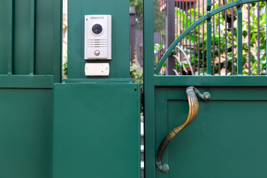 an intercom with a video camera and a microphone for voice communication with a card reader for access by a key card is installed on a green iron gate with handle, close up nobody.