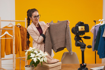 Portrait of contemporary young woman holding knit sweater and smiling at camera while filming video for fashion and beauty channel against yellow background, copy space Wall mural
