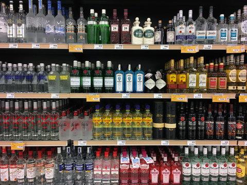 vodka gin tequila and rum bottles on liquor store shelves