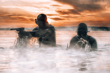 Team of fighters of a special unit move on water to complete the task. The concept of instability, military operations, the cold war.