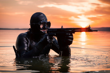The marine comes out of the water and moves toward the target with weapons in hand. The concept of video games, advertising, instability in the world, country conflicts.