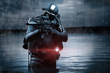 SWAT unit soldier stands waist-deep in water with a machine gun in his hands. The concept of video games, special secret operations.