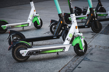 Electric scooter , escooter or e-scooter of the ride sharing company LIME and TIER on sidewalk -  Berlin, Germany - june 2019