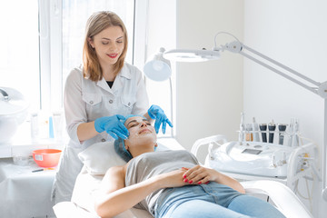 Photo sur Aluminium Spa Woman professional doctor beautician applies a mask on a patient's face for skin care. Cosmetic procedures for skin rejuvenation and nutrition