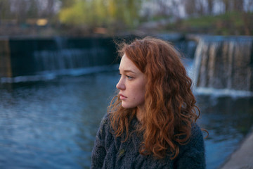 portrait of a girl with red curly hair in a warm sweater against a waterfall