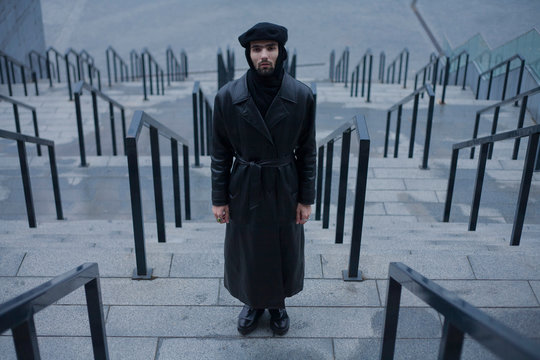 handsome stylish man in a black coat is standing on the steps near the railing on a geometric background