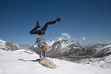 Boy doing a handstand in the mountains.
