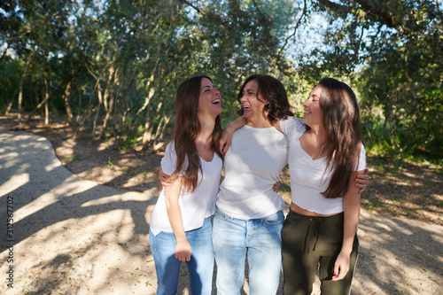 Laughing women embracing and strolling in park