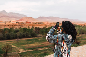 ethnic woman taking photo with smartphone close to a palm tree forest in Morocco