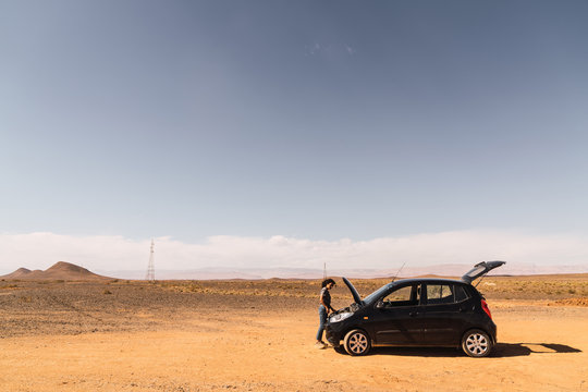 young woman worried repairing her car in a desert road in Morocco
