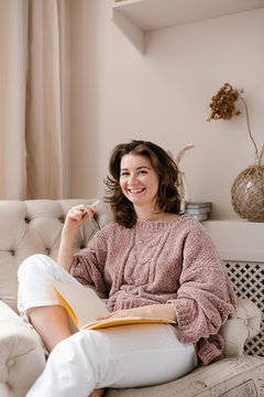 Smiling woman with notebook in armchair