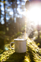 Blank white enamel mug with tea being poured into it on the forest floor