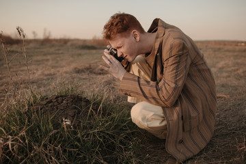 Young man taking picture of dirt pile