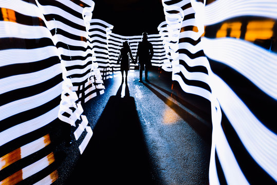 Dark Silhouette Of A Guy And A Girl Standing In Light Corridor