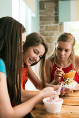 Treat: Girls Looking At Cell Phone While Eating Ice Cream