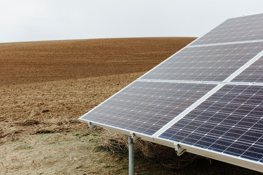 Solar panel with farmland in distance