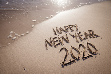 Happy New Year 2020 message handwritten in raised textured letters on a sandy beach with copy space...