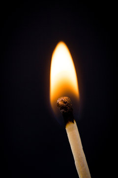 Lighting matches at the moment when it explodes. Burning match over black background. Close up. Copy space.