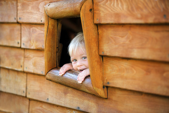 Curious child, toddler boy, peering from a small window in wooden shrub