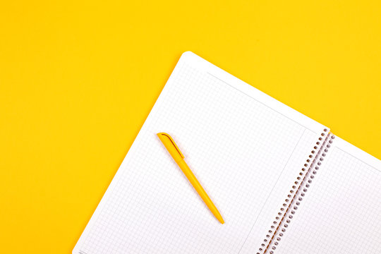 Top view of yellow pen with clean white notebook open with copy space on solid yellow table background for presentation, writer or school education, blogger, novel and friction or brand story concept.