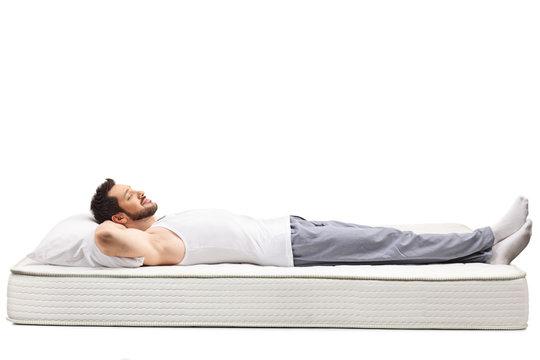 Man in nightwear sleeping on a mattress