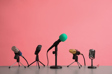 Microphones on table against pink background. Journalist's work