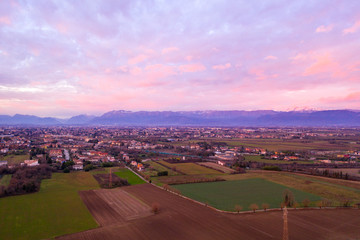 Wall Murals Purple sunset over a small city on a background of mountains view from a drone