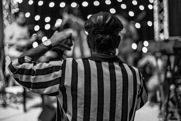 Backside of an adult senior man in the center in improvisation dancing match wearing striped shirt and leather hat. Bokeh lights in the blurred background.