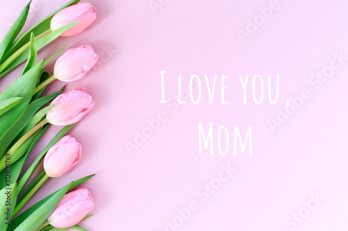 I love you, Mom wording with pink tulips on the pink background. Flat lay, top view. Mother's day holiday celebration card. Horizontal,