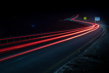 Spoed Fotobehang Nacht snelweg highway long exposure vehicle light trails curvy highway between mountains eilat israel
