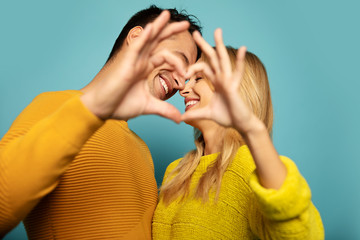 Love time. Close-up photo of man and woman in yellow outfits, who are smiling with their eyes closed, keeping their heads close to each other and making a heart with their hands.